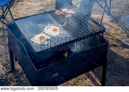Breakfast Camp Cooking. Grilling Crispy Bacon And Eggs On A Cast Iron Plate Over The Camp Fire