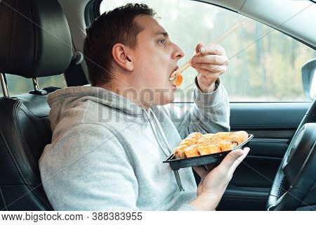 Man Is Eating Sushi, Philadelphia Rolls With Fish, Rice, Salmon, Cream Cheese, Avocado In Car. Fast,