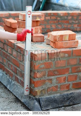 A Mason Person Is Using A Spirit Level To Check If The Surface Of A Brick Foundation Is Even And Lev