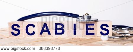 The Word Scabies Is Written On Wooden Cubes Near A Stethoscope On A Wooden Background. Medical Conce