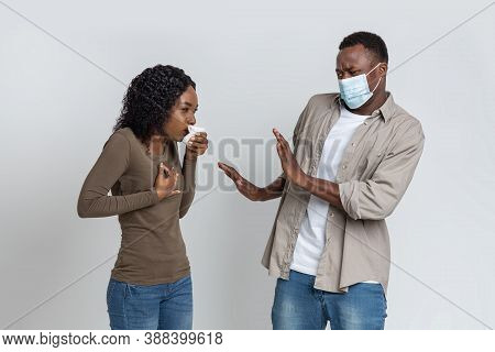 Coronaphobia Concept. Black Guy In Protective Face Mask Afraid Of Coughing Woman, Grey Studio Backgr