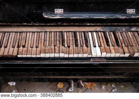 An Old Broken Piano With Dirty Keys Covered In Dust And Soot. Open Keys Of An Abandoned Keyboard Mus