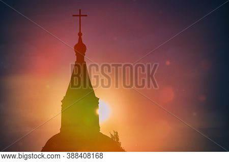 Misty Beautiful Sunset Light Of The Sun Illuminates Catholic Church. Rays Of Light Against The Black