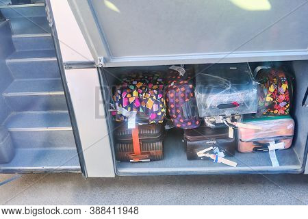 Red And Black Suitcases In The Cargo Compartment Of The Bus. Bags In Compartment Of A Tour Ready To