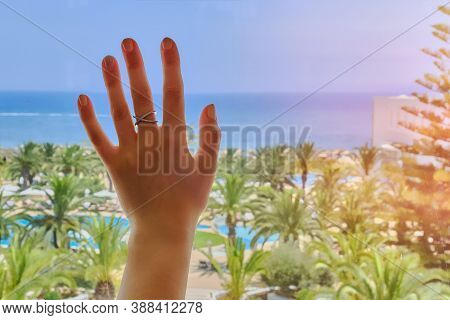 A Woman's Hand On The Glass Window Behind Which You Can See The Sea And A Beautiful Tropical Landsca