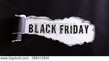 Top View Of Black Torn Paper And The Text Black Friday On A White Background. Black Friday Compositi