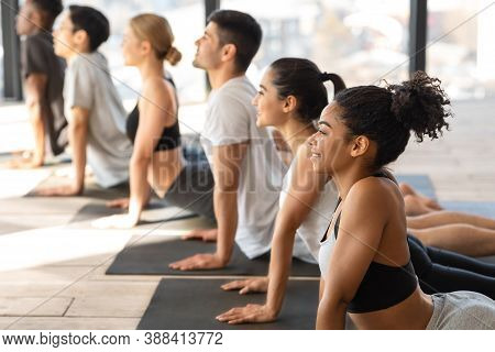 Diverse Multiethnic Men And Women Practicing Cobra Pose During Group Yoga Training Lesson In Modern