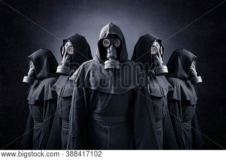 Group of five scary figures with gas masks and hooded cloaks in the dark. Environment pollution.