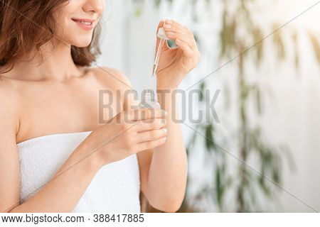 Advertisement For Face Care Products. Cropped Of Unrecognizable Woman Using Serum. Bottle With Face