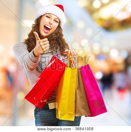 Christmas Shopping. Fashion Girl With Shopping Bags in Shopping Mall showing Thumb up
