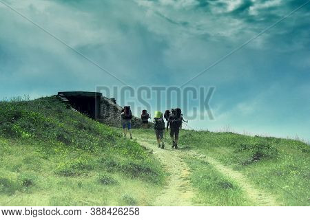A Group Of Tourists Coming To The Dungeon. Hiking In Gloomy Weather. Crypt On Top Of The Hill. Entra