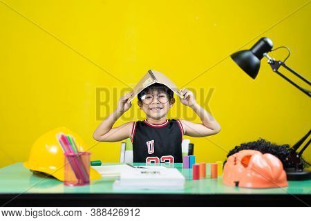 Smiling Boy Wearing Glasses, Take A Book On Top Of The Head, Learning Materials On The Table.
