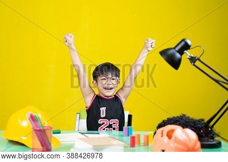 Happy Boy Wearing Glasses, There Are Things For Learning On The Table.