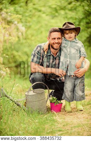 Planting Flowers. Growing Plants. Take Care Of Plants. Boy And Father In Nature With Watering Can. S