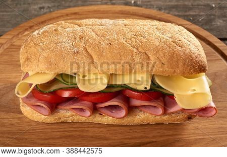 Sandwich With Ciabatta Bun, Thin Slices Of Sausage And Edam Cheese On Brown Wooden Board, Top View