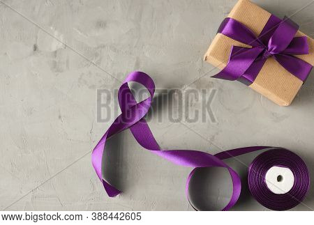 Gift Wrapped In Brown Kraft Paper And Tied With A Purple Silk Bow, Gray Table, Copy Space