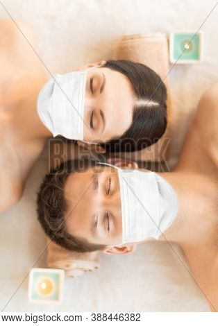wellness, bodycare and health concept - couple wearing face protective medical mask for protection from virus disease at aromatherapy at spa session
