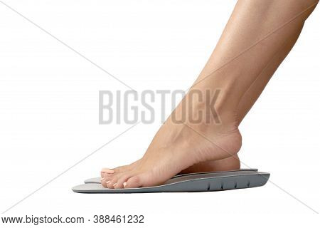 Beautiful Female Feets And Insoles Isolated On A White Background. The Girl Tries On Orthopedic Inso