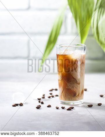 Cold Brewed Iced Coffee In A Tall Glass Cup And Coffee Beans On A Gray Concrete Background. Pouring