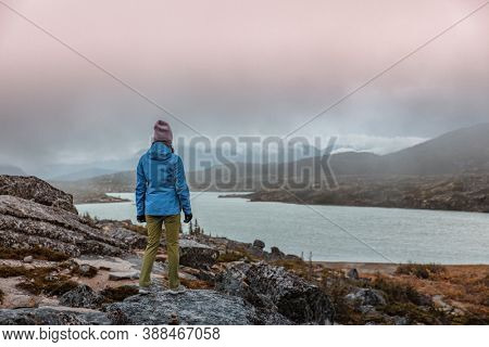 Travel alone in Alaska during cold autumn weather. Woman tourist hiking near lake in the North.