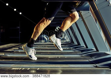 Cropped Shot Of Athletic Man In Sportswear Running On A Treadmill In A Gym, Focus On Legs