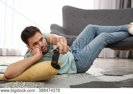 Lazy Young Man Playing Video Game While Lying On Floor At Home