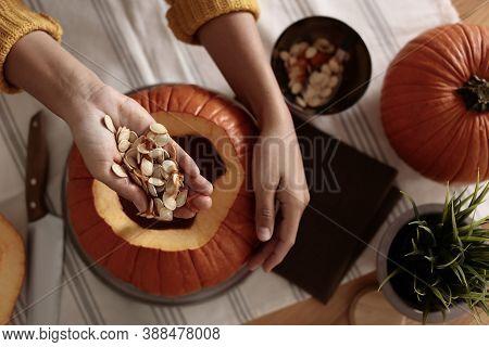 Woman Making Pumpkin Jack O'lantern At Table, Top View. Halloween Celebration