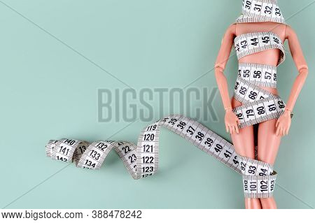 Doll Wrapped In Measuring Tape. Tied Up Plastic Doll, Weight Loss, Fasting And Slimming, Diet, Anore
