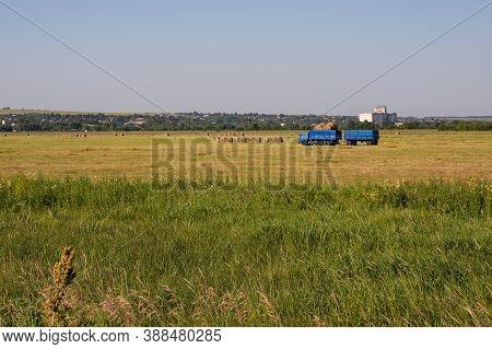 Nizhny Novgorod Region, Russia - July 8, 2020: Blue Truck With A Trailer Carrying Rolls Of Hay, Autu