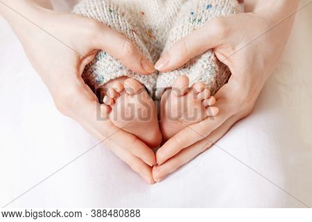 Baby Feet In Mother Hands. Tiny Newborn Baby's Feet On Female Heart Shaped Hands Closeup. Mom And He