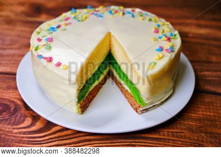Three-color Cake On A Wooden Table. A Plate Of Dessert With Layers Of Green, Brown And White. Sprink