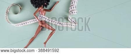 Doll Wrapped In Measuring Tape. Tied Up Unrecognizable Plastic Doll, Weight Loss, Fasting And Slimmi