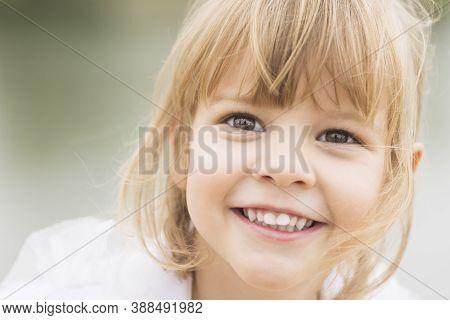 Beautiful Close-up Child Portrait Of Smiling Joyful Blond Hair Little Girl.