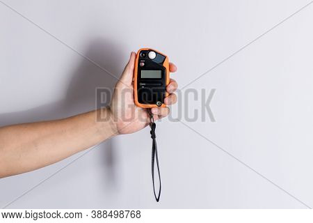 Hand Holding Light Exposure Meter, A Photograph Device For Measuring Illumination On White Backgroun