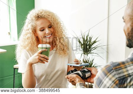 Woman Customer Of Coffee Shop Paying For Coffee Through Mobile Phone Using Contactless Technology