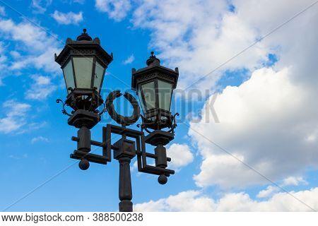 City Decorative Street Lantern On Cloudy Sky Background. Urban Metal Lamppost In Retro Style
