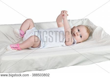 A Four-month-old Baby In White Clothes Is Lying On His Back On A Changing Table. The Arms And Legs A