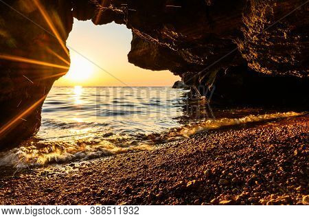 A Small Cave By The Sea During Sunset. Bright Rays Of The Sun Shine Into The Cave. Focus On Pebbles