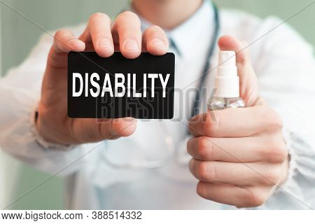 Doctor Holding A Paper Card With Text Disability And The Medicine Bottle, Medical Concept