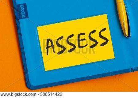 The Words Assess Is Written In Black Marker On The Yellow Paper For Notes.