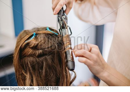 Beauty, Hairstyle Concept, Happy Young Woman And Hairdresser With Hair Iron Making Hairdo At Hair Sa