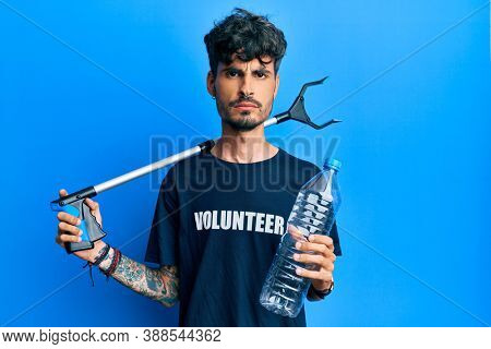 Young hispanic man holding plastic bottle and litter picker to recycle skeptic and nervous, frowning upset because of problem. negative person.