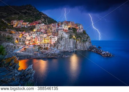 Amazing scenery of Manarola town by the Ligurian Sea with thunderstorms , Italy