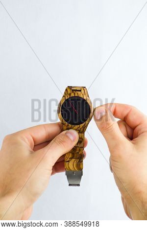 A Man Stretches Out A Wristwatch And Adjusts The Time.
