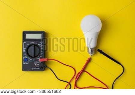 Dark Digital Multimeter With Probes And Led Bulb On Yellow Background. Power Saving Concept. A Multi