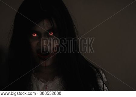 Female Zombie In Blood. Closeup Face And Eyes Of Asian Woman Ghost With Blood. Horror Creepy Scary F