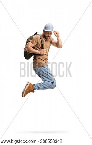 Full length shot of a guy with a backpack jumping and holding his cap isolated on white background