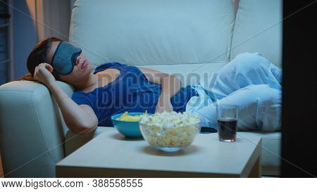 Woman Sleeping With Eye Covering Mask In Front Of Tv Lying On Couch. Tired Exhausted Lonely Sleepy L