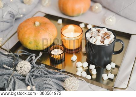 Metal Tray With Hot Chocolate And Melted Marshmallow In A Black Mug, Burning Aroma Candles And Pumpk