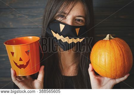 Halloween 2020 Trick Or Treat. Happy Female In Black Evil Face Mask Holding Pumpkin And Jack O Lante